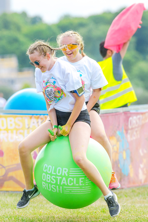 fmale: STOCKHOLM, SWEDEN - JULY 22, 2017: Jumping with big rubber balls at the color obstacle rush at Gardet in Stockholm. 15 obstacles, 6 colors and 5k running.