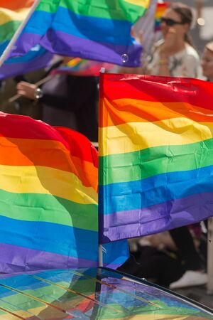 STOCKHOLM SWEDEN, 5 AUG, 2017: Closeup of Rainbow flags at the Pride parade in Stockholm with happy people and waving flags. Aprox 45 000 participants in the parade.