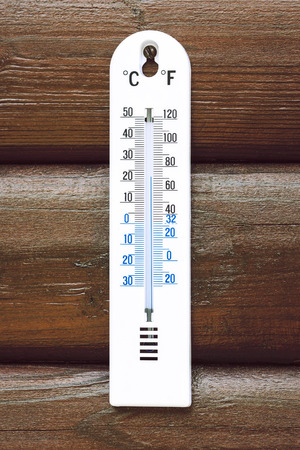 White Thermometer On A Brown Wooden Wall 22 Degrees Celsius Stock