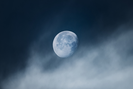 Moon with light clouds in its waning gibbous phase during morning. Dramatic view during early morning