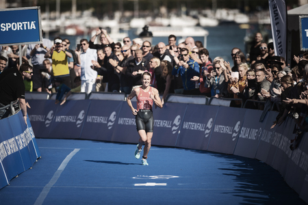 STOCKHOLM, SWEDEN - AUG 26, 2017: Winner Flora Duffy (BER) running into the finish area with the crowd cheering at the womens ITU triathlon series. Female Olympic distance.