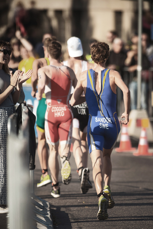 STOCKHOLM, SWEDEN - AUG 26, 2017: Gabriel Sandor (SWE) running in a group trough the streets of the old city at the ITU triathlon series for men. Olympic distance Editorial