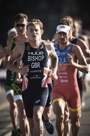 STOCKHOLM, SWEDEN - AUG 26, 2017: Thomas Bishop (GBR) leading a group running trough the streets of the old city at the ITU triathlon series for men. Olympic distance