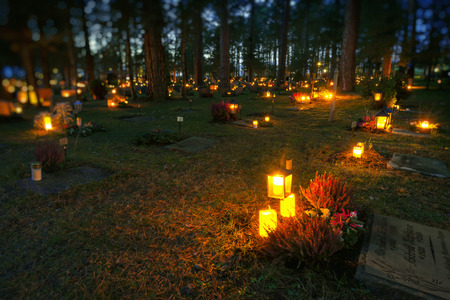 STOCKHOLM, SWEDEN - NOV 4, 2017: Candlelights at the graves at the Woodland cemetary or Skogskyrkogarden during All saints night. 4th of November.