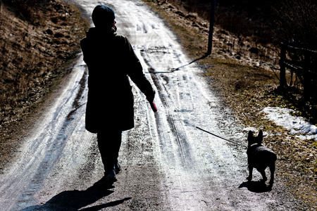 SODERTALJE, SWEDEN, APRIL, 2, 2018: Silhouette of a woman walking wjith her french bulldog at a wet spring road.