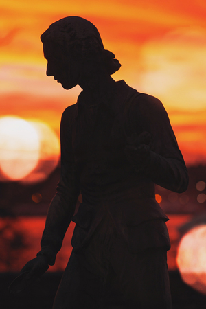 STOCKHOLM, SWEDEN - DEC 30, 2016: Silhouette at statue of Carl von Linne at Waldermarsudde in colorful sunset light