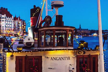 STOCKHOLM, SWEDEN - NOV 25, 2018: Angantyr steamboat from Stromma Kanalbolaget embarked with christmas lights at Nybrokajen during the night. Editorial