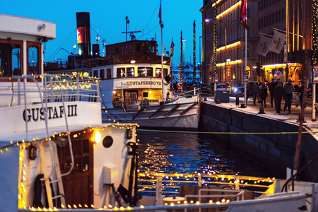 STOCKHOLM, SWEDEN - NOV 25, 2018: Steamboats Gustaf III and Gustafsberg VII from Stromma Kanalbolaget embarked with christmas lights at Nybrokajen during the night.