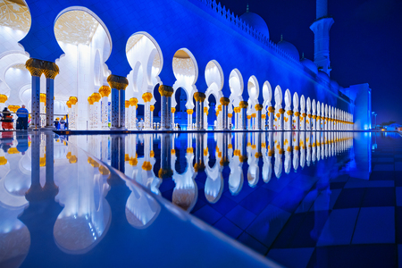 ABU DHABI, UAE - JAN 22, 2019: Sheikh Zayed Mosque or the grand Mosque during evening with a row of white arcs mirrored in the outside pond. Redakční