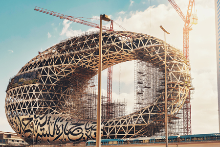 DUBAI, UAE - JAN 20, 2019: The construction of the Museum of the Future one of the world's most advanced buildings. Metro passing by. Opening 2019 Editorial
