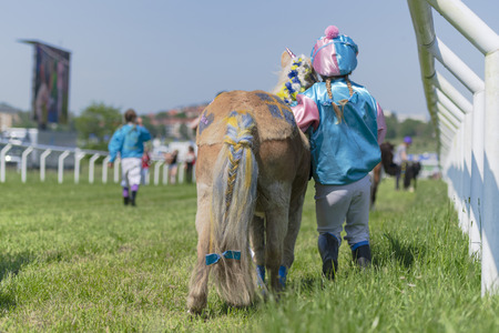 STOCKHOLM, SWEDEN - JUNE 6, 2019: Pony racing during sunny weather at Nationaldags Galoppen in Gardet field in the middle of Stockholm. Editöryel