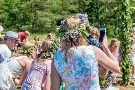 SINGO, SWEDEN, JUNE 21, 2019: Midsummer with women wearing wraths during a clear and sunny day in Sweden.
