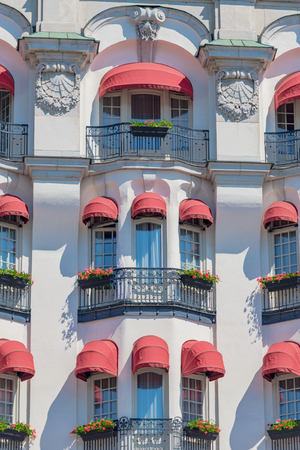 STOCKHOLM, SWEDEN 29 JUNE, 2019. Red colorful blinders at the white ornamented hotel Diplomat with french balconys facing Strandvägen in Stockholm during summer.