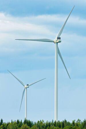 Turbine eoliche che girano sopra una foresta di pini e un cielo nuvoloso. Svezia Archivio Fotografico