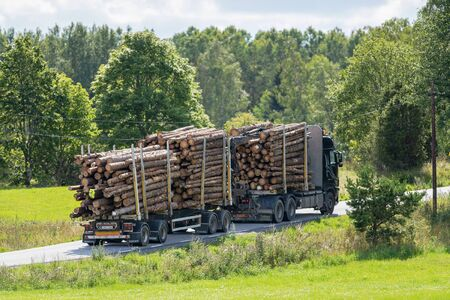 GRISSLEHAMN, SWEDEN, AUG 14, 2019: Truck with stacked timber going thru the green landscape during summer.