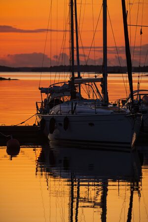 Sailboats moored for the evening at a marina, silhoutte in the orange sunset during summer. Sweden Reklamní fotografie