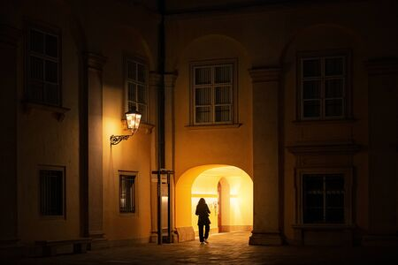 Woman walking thru a old yellow passway during evening hours in the Hofburg palace complex. Vienna, Austria