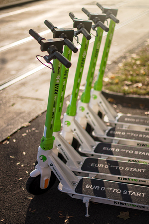 VIENNA, AUSTRIA, OCTOBER 26, 2019: Green Electric Scooters provided by Kiwiride standing in a row in the morning. Schwedenplatz
