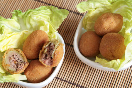 Fried olives typical of Marche region filled with meat, on a bed of lettuce in two whites bowls