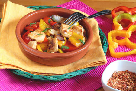 Delicious chicken with red and yellow peppers in a rustic bowl with a fork above it photo
