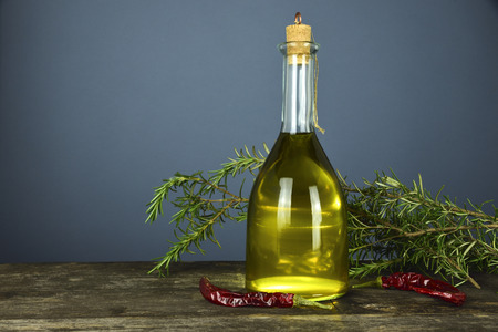 The bottle on the wooden table contains extra virgin olive oil produced in Italy. Chili, garlic and rosemary are the aromatic herbs that often accompany the oil in the seasoning of the dishes