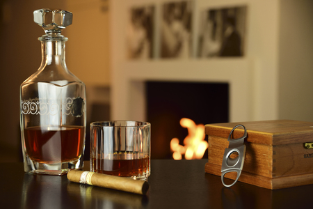 enveloping environment heated by the fire in the fireplace. in the foreground a glass of liquor, a bottle and a cigar Stock Photo