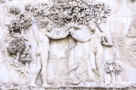 Detail of the facade of the Duomo of Orvieto, Italy. Marble bas-relief representing episodes of the bible.Adamo and Eva capture the apple instigated by the snake