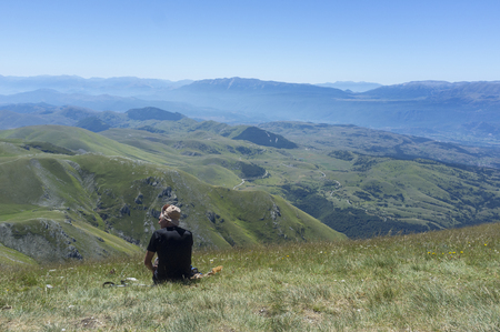 man sitting on the grass looking at the mountains of the Apennines