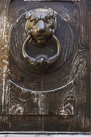Detail of the knocker of an old wooden door Stock Photo