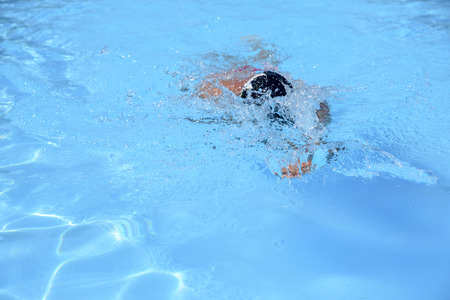 Caucasian man swims in freestyle in an outdoor pool on a sunny day. The man is wearing a red swimsuit and a black cap. fit man swimming during leisure