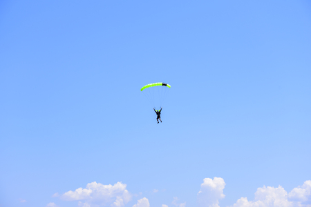 parachutist descends into the blue sky on a sunny day