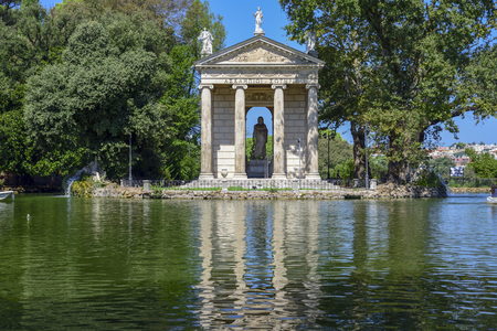 Garden of Villa Borghese. Lake with boats and temple of Esculapio.Rome Italy