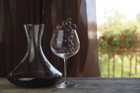 Italian red wine inside the decanter and goblet with decorations. Natural background