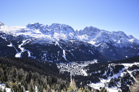 The village of Madonna di Campiglio in the valley, nestled between the peaks of the Italian Alps covered with snow