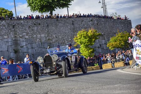 Amelia, Italy, May 2018. Mille Miglia (1000 Miles), historical vintage car race. Two men driving a historic Bugatti, blue color. On the road