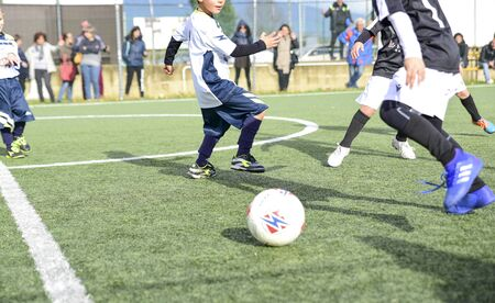 three young football players. Children play a soccer game. Legs in action with a ball. Stock Photo
