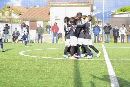 jóvenes futbolistas. Los niños juegan un partido de fútbol. Los niños pequeños animan el gol. Foto de archivo