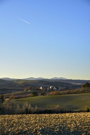 farm in the hills in the warm light of sunset. Countryside and agriculture in winter