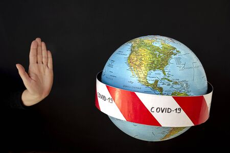 Stop the coronavirus. Hand imposes stop to spread of coronavirus, COVID-19. Planet earth with caution barrier tapes. In the foreground the United States, Canada and Mexico. Black background
