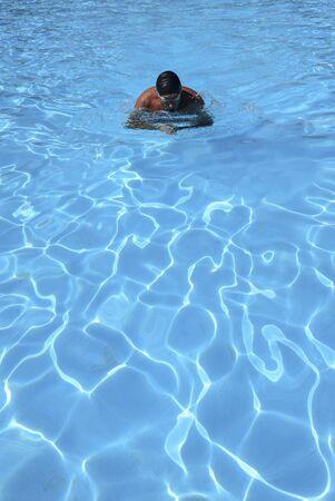 uomo caucasico nuota in stile rana in una piscina all'aperto in una giornata di sole. L'uomo indossa un costume da bagno rosso e un berretto nero. uomo in forma che nuota durante il tempo libero