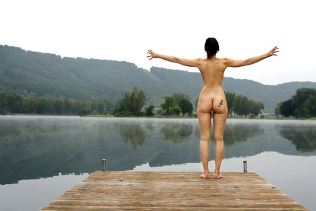 Young nude woman at the lake on a misty autumn morning