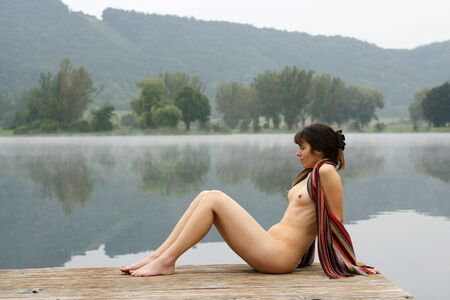 Young nude woman at the lake on a misty autumn morning Stock Photo - 4125431