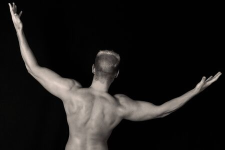 Muscular Back of a Bodybuilder over Black photo