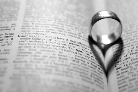 christian marriage: Word LOVE in a dictionary next to a heart-shaped shadow cast by a ring