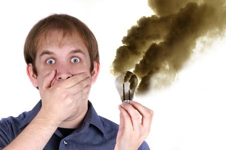 Young man looking shocked because auf lightbulb emitting acid vapor - Picture Series photo