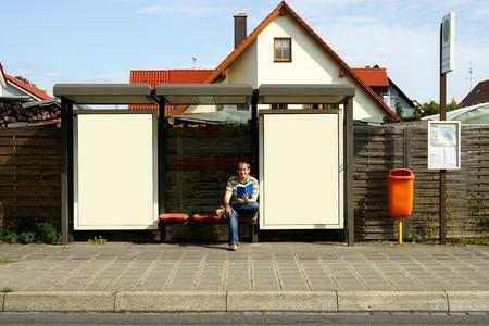 parada de autobus: machos j�venes estudiante sentado en parada de autob�s con carteles en blanco