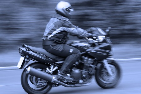 adrenaline rush: blurred motorcyclist in blue Stock Photo
