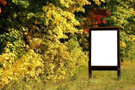 posting: billboard next to autumnly colored trees