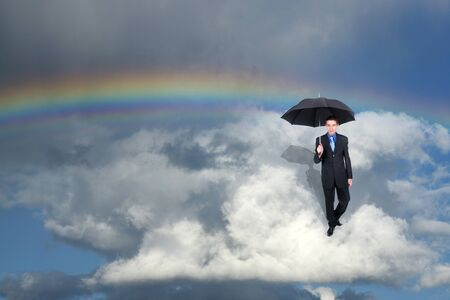Businessman holding an umbrella while wanderin the clouds  photo