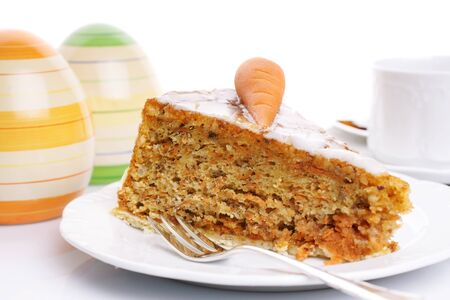 Slice of carrot cake on a white plate over bright background